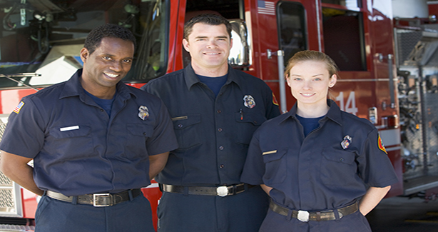 Three FEMS employees in front of fire truck.